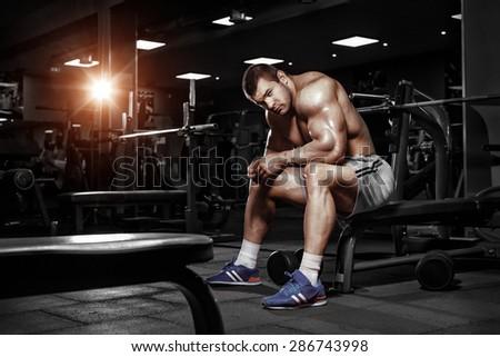 Athlete muscular brutal bodybuilder emotional posing in the gym  - stock photo