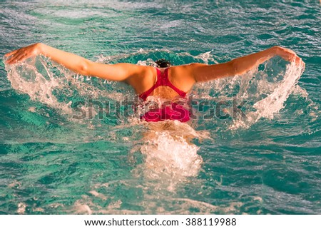 Athlete on a pool swimming the butterfly swimming technique. - stock photo
