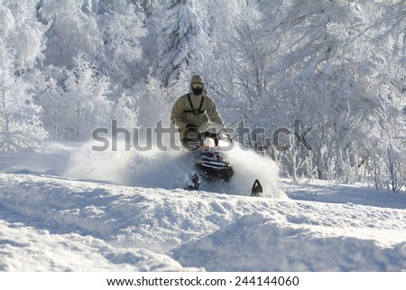 Athlete on a snowmobile moving in the winter forest in the mountains of the Southern Urals. - stock photo