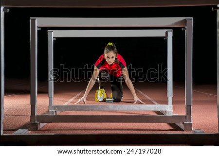 athlete on the starting block in hurdles race - stock photo
