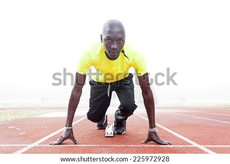 athlete on the starting blocks - stock photo