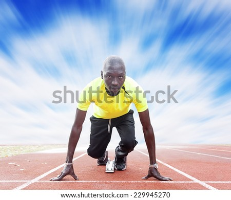 athlete on the starting blocks under cloudy sky - stock photo