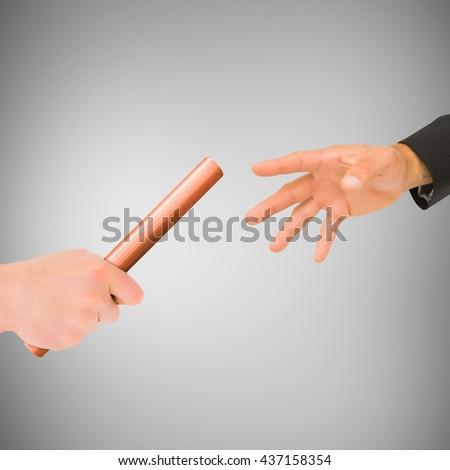 Athlete passing a baton to businessman on grey background - stock photo