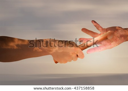 Athlete passing a baton to the partner against cloudy sky - stock photo