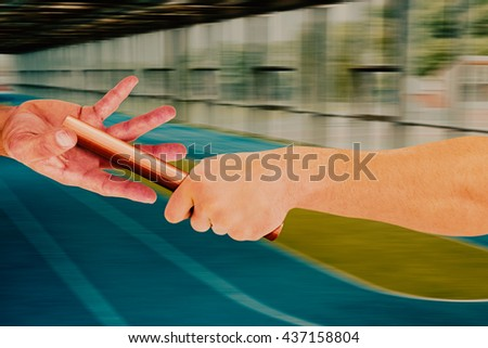 Athlete passing a baton to the partner against tracks - stock photo