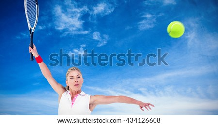 Athlete playing tennis with a racket against blue sky