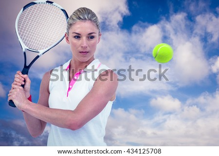 Athlete playing tennis with a racket against blue sky with white clouds
