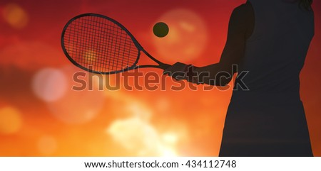 Athlete playing tennis with a racket against landscape with sunset