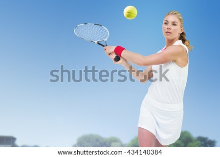 Athlete playing tennis with a racket against view of a playing field against blue sky
