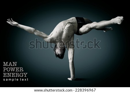Athlete.Power.Energy.Gym.Men's sports figure.Circus actor stand on one hand  on a black background.Black-and-white image