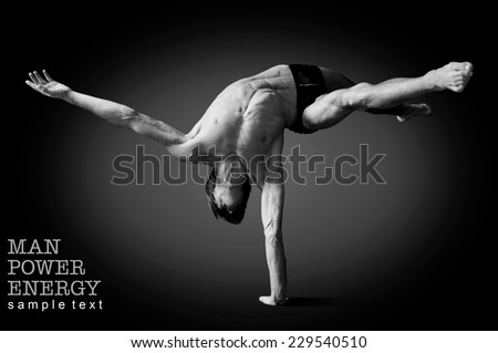 Athlete.Power.Energy.Gym.Men's sports figure.Circus actor standing on the hand on a black background.Black-and-white image