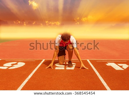 athlete ready at the start of a running track on sunset background with fog. - stock photo