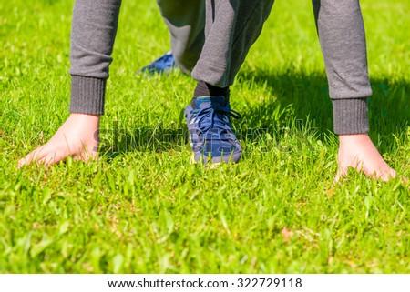 Athlete ready to run on the green lawn - stock photo