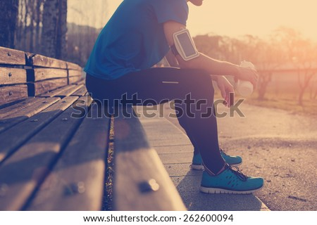 Athlete resting on bench in park at sunset after running with bottle of water (intentional sun glare and vintage color) - stock photo