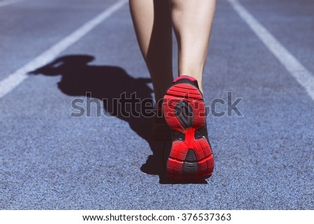 Athlete runner feet down stadium track. Closeup on female shoe and legs. Woman summer fitness workout. Jogging, sport, healthy active lifestyle concept.