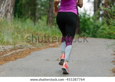 Athlete runner feet running on road close up on shoe. woman fitness jog workout wellness concept. - stock photo