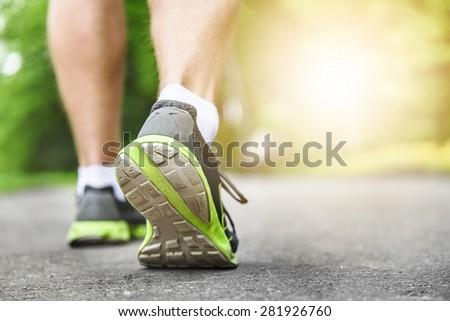 Athlete runner feet running on road closeup on shoe. Man fitness sunrise jog workout wellness concept. - stock photo
