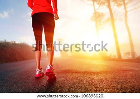 Athlete runner feet running on road closeup on shoe. woman fitness sunrise jog workout wellness concept. - stock photo