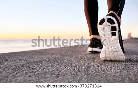 Athlete runner feet running on treadmill closeup on shoe. Jogger fitness shoe in the background and open space around him. Runner jogging training workout exercising power walking outdoors in city. - stock photo
