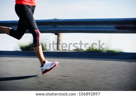Athlete runner motion blur running on road focus on shoe. woman speed sprint fitness training.