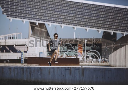 Athlete runner training at road in sportswear at central position. Muscular fit sport model sprinter exercising sprint on city road. Full body length of Caucasian model. - stock photo