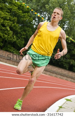 Athlete running a middle distance race on an oval track - stock photo