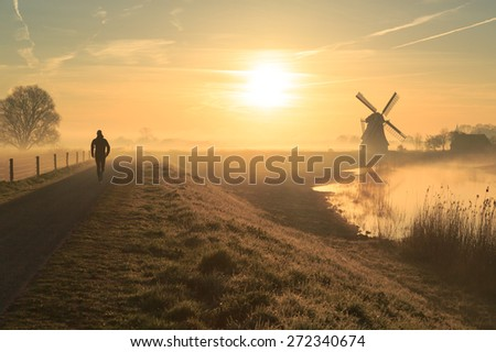 Athlete running in the foggy, Dutch countryside near a windmill just after sunrise. - stock photo