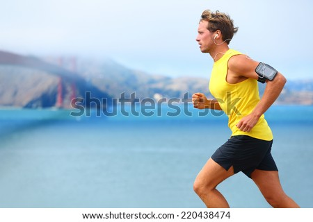 Athlete running man - male runner in San Francisco listening to music on smartphone. Sporty fit young man jogging by San Francisco Bay and Golden Gate Bridge. Jogger training with smart phone armband, - stock photo