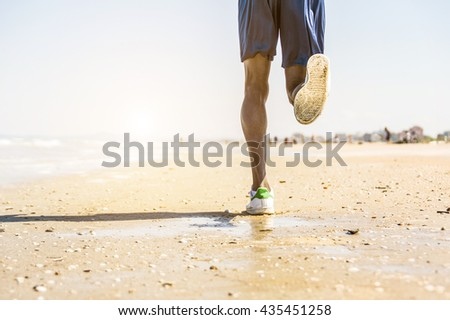 Athlete running man - Sporty fit young black man jogging at the beach. Close up of his legs. - stock photo