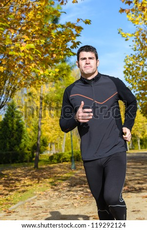 Athlete running on autumn park. Sportsman exercising outdoors with trees on background. - stock photo