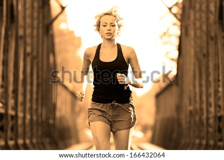 Athlete running on railway tracks bridge in morning sunrise training for marathon and fitness. Healthy sporty woman exercising in urban environment before going to work; Active urban lifestyle. - stock photo