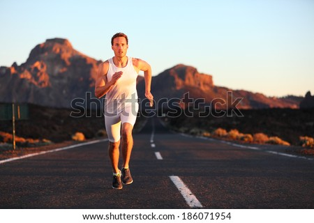 Athlete running sprinting at sunset on road. Male runner training in mountain landscape at night. Fit young muscular fitness sport model in his 20s. - stock photo