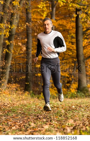 athlete running through the forest - stock photo