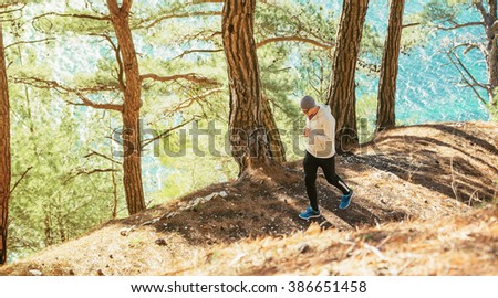 Athlete running through the woods on a background of the sea