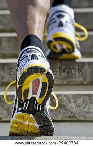 Athlete runs up the stairs - stock photo