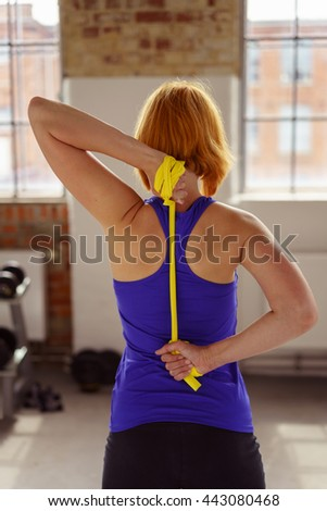 Athlete stretches yellow band behind her back while exercising in brightly lit fitness center