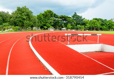 Athlete Track or Running Track with Black and white hurdles  nice scenic tree and clouds  - stock photo