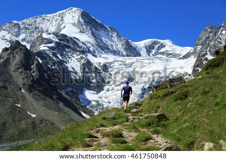 Athlete trail running in the beautiful mountains of Wallis, Switzerland. Sports and healthy lifestyle concept.