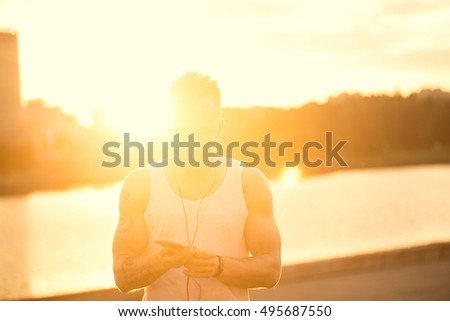 Athlete trail running silhouette of a man runner at sunset sunrise.Cardio fitness training of marathon race sportswoman.Active healthy lifestyle.Smart Watch on hand. Telephone with music for training