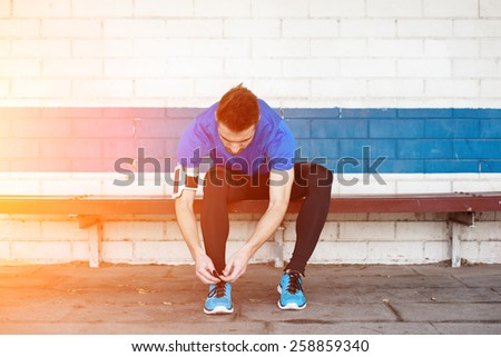 athlete tying shoelaces and preparing for running (intentional sun glare) - stock photo