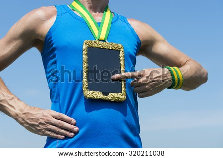 Athlete using tablet hanging as gold medal against blue sky - stock photo