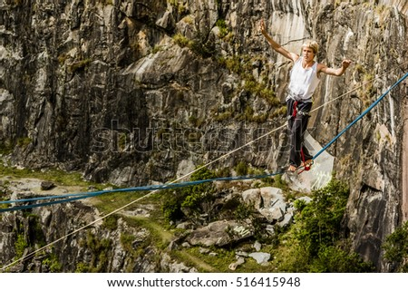 Athlete walking in highline, slackline, tight rope in a rock mountain