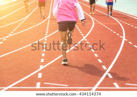 athlete warm up on running track at the stadium  in the morning. - stock photo