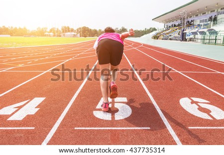 athlete warm up on running track at the stadium in the morning - stock photo
