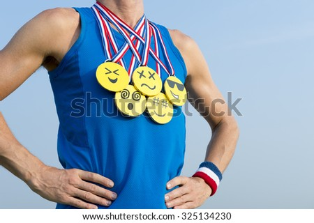 Athlete wearing gold medals with bright yellow emoji faces standing in front of blue sky background - stock photo