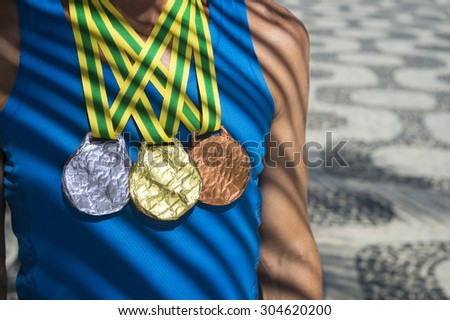 Athlete wearing gold, silver, and bronze medals standing under palm frond shadows on Ipanema Beach  - stock photo