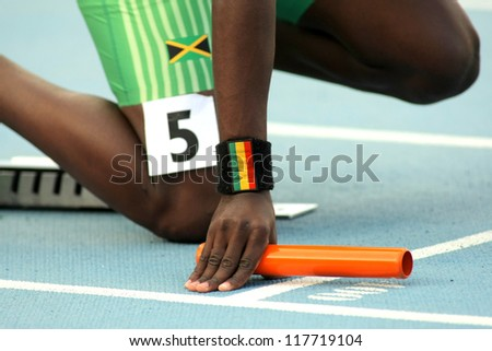 Athlete with a baton on the start of relay event - stock photo