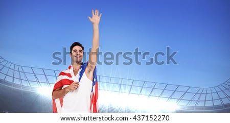 Athlete with american flag wrapped around his body against large football stadium under bright blue sky - stock photo