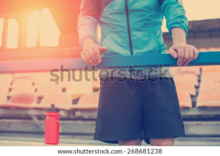 athlete with bottle of water holding railing (intentional sun glare and vintage color) - stock photo
