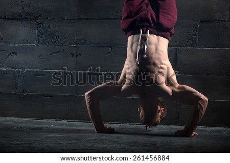 Athlete with naked torso doing push-ups on his hands while standing upside down near the concrete wall. Studio shots in the dark tone. - stock photo